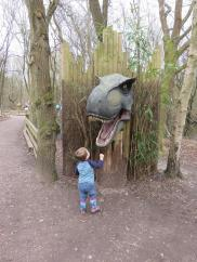 child looking at dinosaur statue
