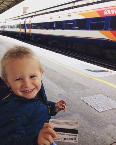 child excited with a train behind him