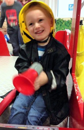smiling child dressed as fireman