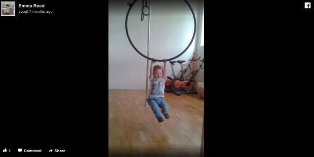 child hanging from an aerial hoop