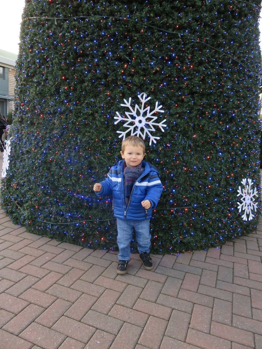 child in front of christmas tree